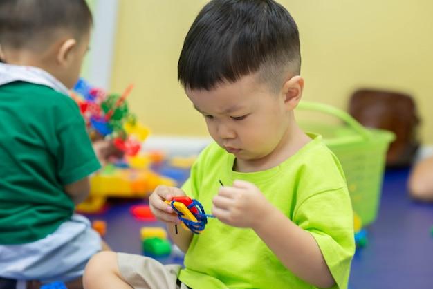 部屋で一緒におもちゃを遊ぶ男の子 Premium写真