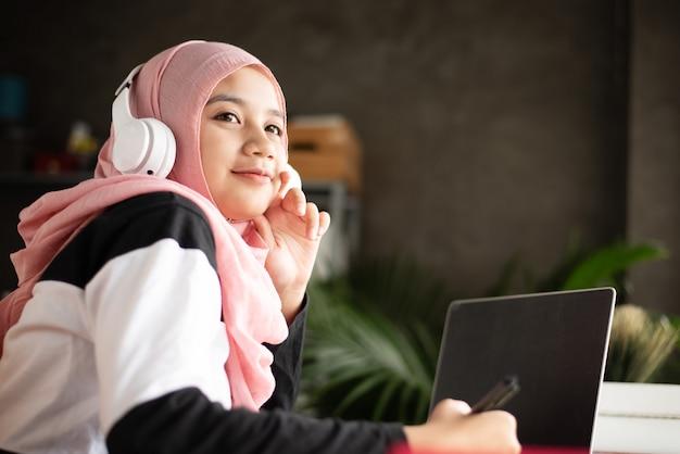イスラム教徒の女性がペンを手に持って、彼女の頭にワイヤレスヘッドフォンを置き、プロジェクトについて考えるために外を見て、自宅で仕事をして、木製の机の上のラップトップをぼやけ、 Premium写真