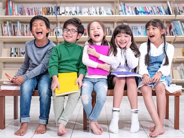 Пятеро умных детей, сидящие на деревянном стуле, с чувством счастья, наслаждаются со своим классом в школе. Premium Фотографии