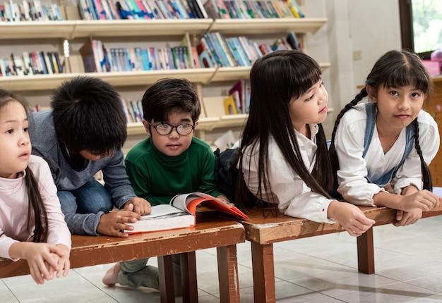 Пять маленьких детей кладут деревянный стол, играют и делают деятельность вместе, счастливый момент в школе, расплывчатый свет вокруг Premium Фотографии