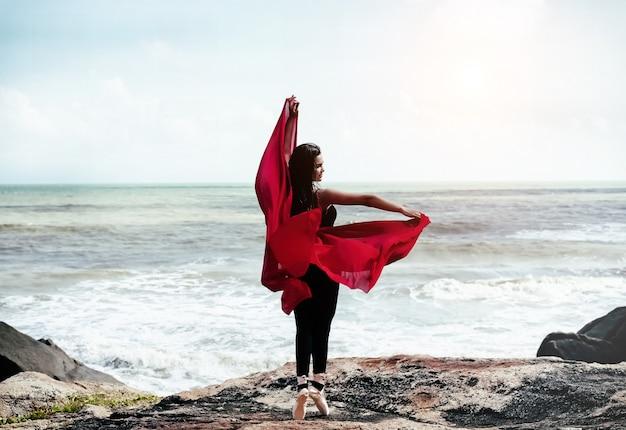 赤いスーツとサテンのバレエシューズを着ている美しさの女性の抽象芸術デザインの背景 Premium写真