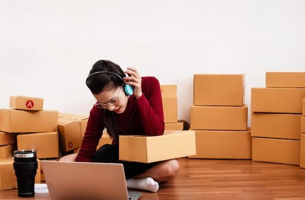 女性のホームオフィス、中小企業の所有者で働いて、ラップトップからの注文をチェック Premium写真