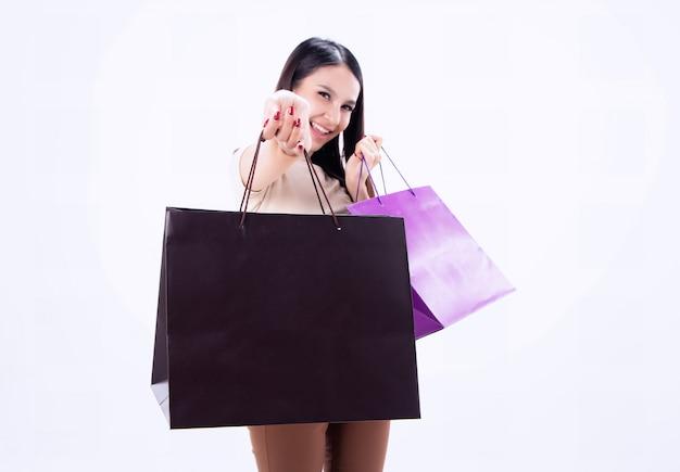 Сумка для покупок крупным планом показывала рукой нечеткой красавицы, с улыбкой и счастливым лицом, шопоголика Premium Фотографии
