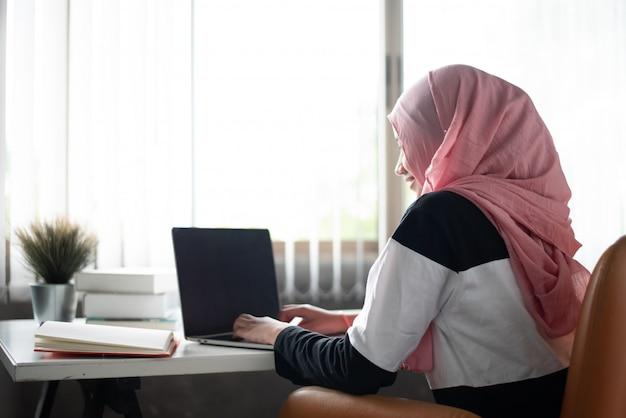 木製の椅子に座って、自宅で仕事をして、窓の横にある木製の机の上のノートパソコンと本を使用して、イスラム教徒の女性 Premium写真