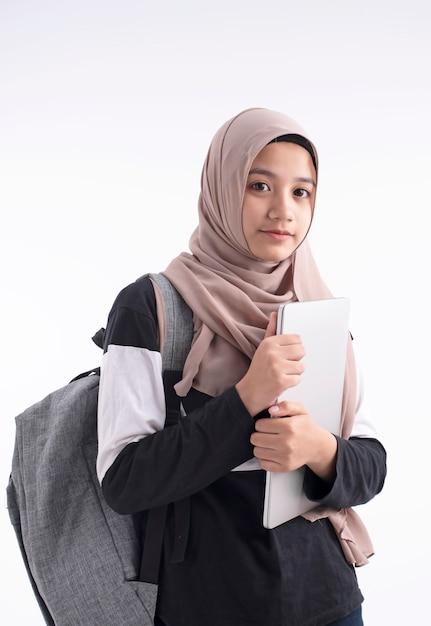 ノートパソコンを手に保持している美しいイスラム教徒の女性 Premium写真