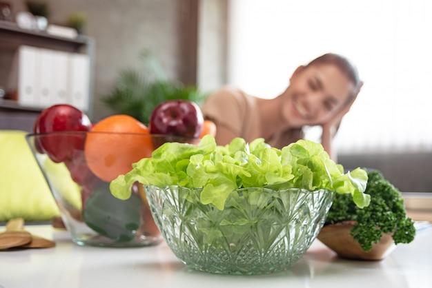 В селективном фокусе зеленых овощей в большой удар, перед затуманенное красивая женщина Premium Фотографии