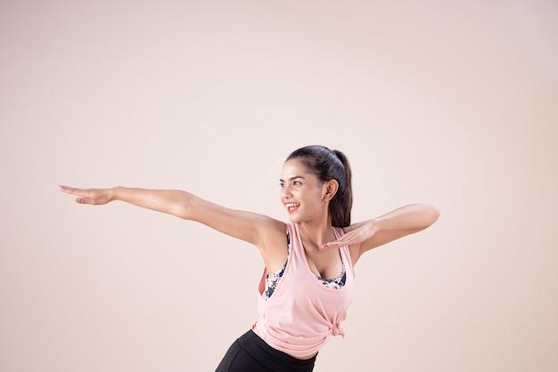 Молодая женщина в костюме для упражнений, поднимая руки вверх в воздухе, делая танцевальные работы Premium Фотографии