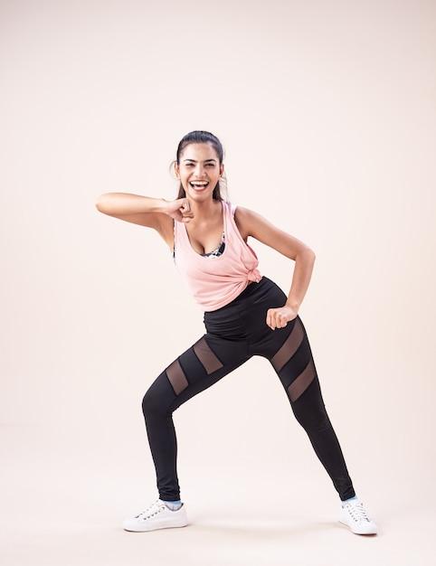 Молодая женщина носить спортивный костюм, делая танцевальные тренировки, для упражнений Premium Фотографии
