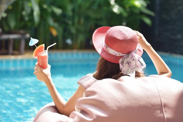 スパのスイミングプールでリラックスできる魅力的な若い女性のビューを閉じます。旅行、幸福の感情、夏の休日の概念。 Premium写真