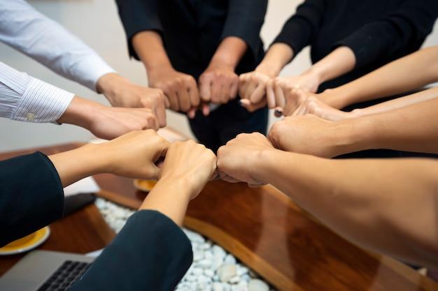 若いグループは、チームワーク、成功、コンセプトのための団結とライン接続への手を象徴する、仕事の成功、手を動かすための手を組んでいます。 Premium写真