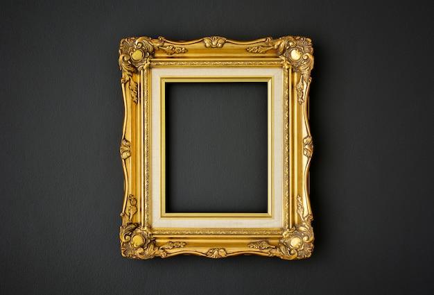黒い色の壁の背景にゴールドのビンテージ写真フレーム Premium写真