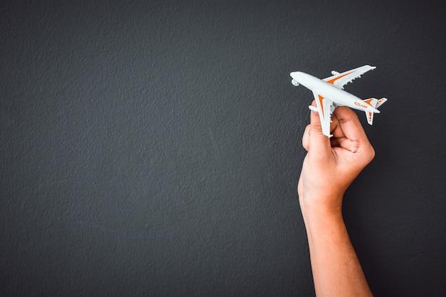 黒い色の壁の背景の上の白いおもちゃの飛行機モデルを持っている男の手 Premium写真