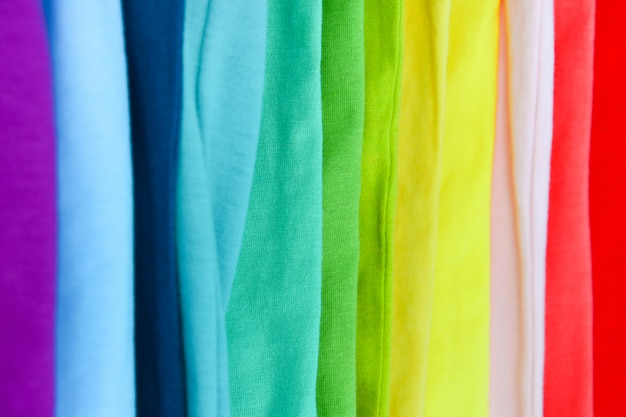 Коллекция красочных радужных футболок висит на вешалке в шкафу Premium Фотографии