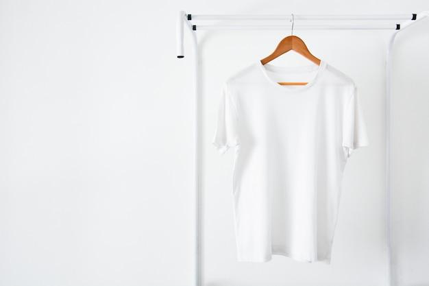 Белая футболка висит на деревянной вешалке Premium Фотографии