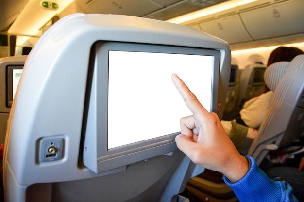 Пальцы, указывающие на белый пустой жк-монитор за пассажирским сиденьем на самолете Premium Фотографии