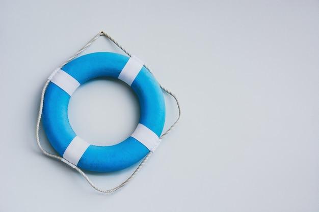 Синий и белый безопасный тор или спасательный круг, висящий на белом фоне стены, копия пространства Premium Фотографии