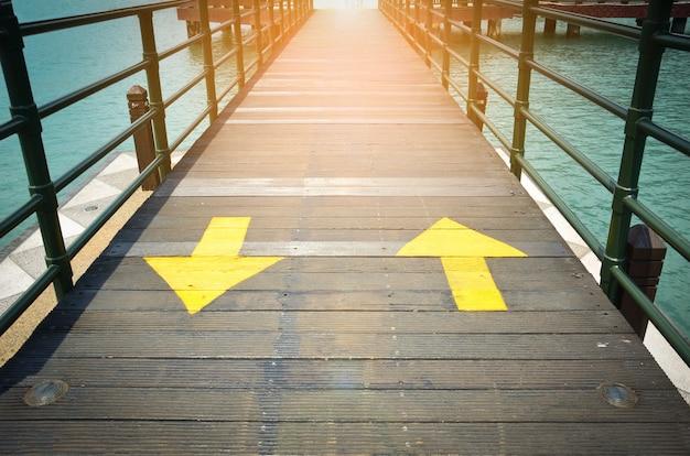 Двухсторонние желтые стрелки движения, указывающие на два направления на деревянном мосту Premium Фотографии