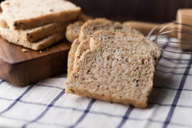 全粒小麦、暗い木の板に全粒粉パン、クローズアップ、トップビュー Premium写真