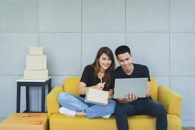 スマイリーフェイスとカジュアルな服装で若い幸せなアジアビジネス不機嫌そうなカップルはラップトップを使用して、彼らのスタートアップのホームオフィス、配達店で小包箱に顧客の名前と住所を書く Premium写真