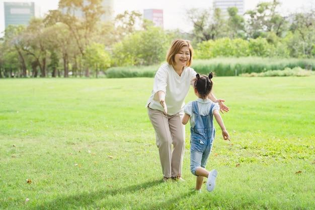 アジアの祖母と孫が公園で一緒に幸せな時間を過ごして Premium写真