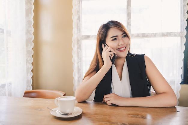 若い魅力的なアジアビジネスの女性が呼び出しているか、カフェでスマートフォンを使用 Premium写真