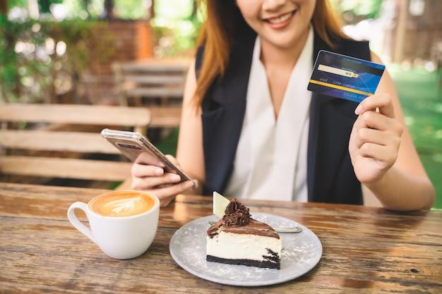 若い魅力的な幸せなアジア女性のトリミングされた画像は、タブレットまたはスマートフォンを使用しています Premium写真