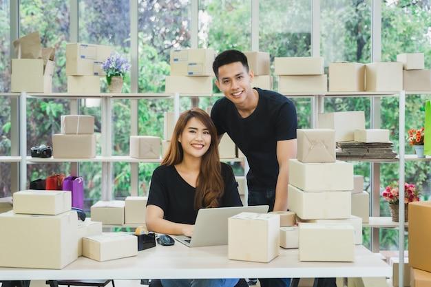 カメラを探しているオンライン中小企業の若い幸せなアジアビジネスカップル所有者の肖像画 Premium写真