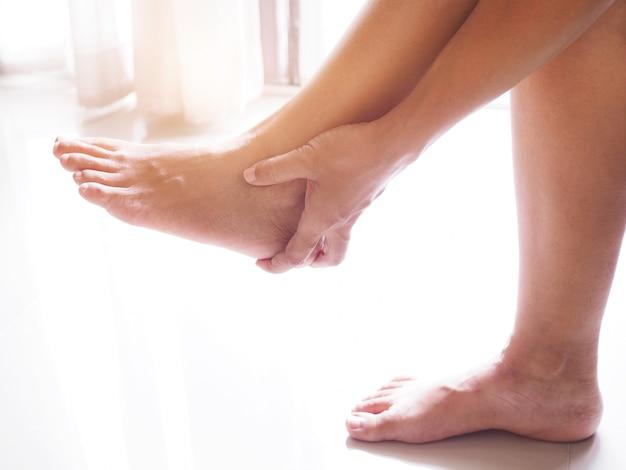 アジアの女性は手を使ってかかとの痛み、慢性的な痛みを伴う足の損傷に苦しんでかかとをマッサージします Premium写真