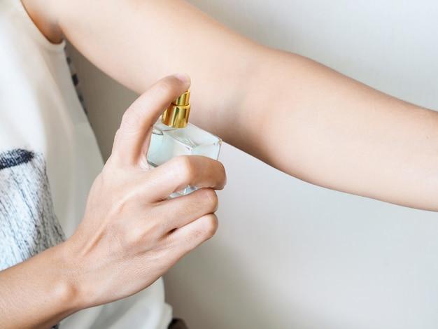 腕に香水をスプレーする女性のクローズアップ体に香りを追加します。 Premium写真