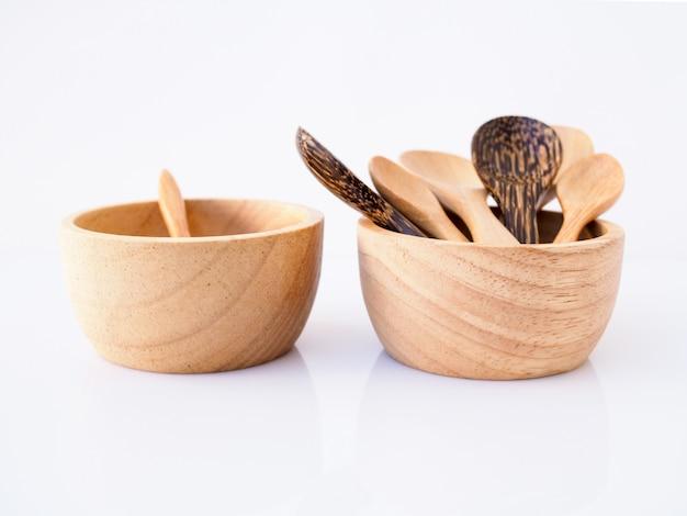 カップ、ボウル、白い表面に分離されたタイから手作りの木製スプーン入りスナック。 Premium写真