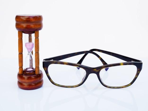 砂時計と白い表面に分離された眼鏡、目の健康、限られた時間の概念の世話をするタイミングのカウントダウン。 Premium写真