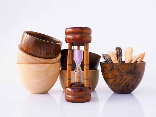 砂時計と手作りの木製ダイニングカップ、ボウル、スプーン、白い表面、食事の健康管理の時間に分離された調理器具セット。 Premium写真