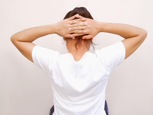 手を上げて筋肉を伸ばし、後頭部に触れて腰痛や頭痛を和らげる運動姿勢のアジア人女性。 Premium写真