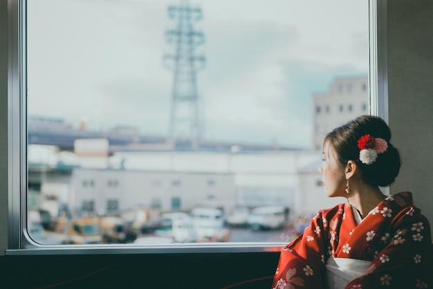 窓の近くに座って日本の古典的な電車で旅行着物を着ているアジアの女性 Premium写真