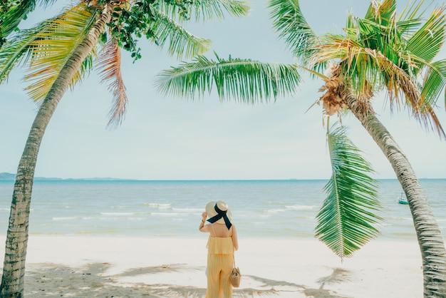 Женщина, наслаждаясь пляжного отдыха радостным летом на тропической голубой водой. Premium Фотографии