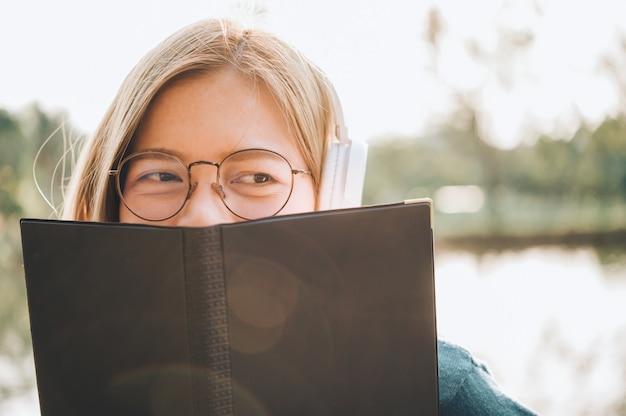 本を読んで、日光、都市ライフスタイルコンセプトに対して屋外公園でヘッドフォンで音楽を聴く眼鏡の女性の笑みを浮かべてください。 Premium写真