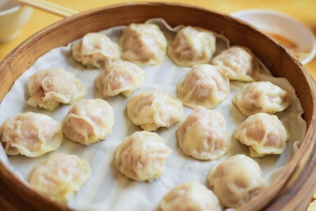 シャオロングバオは、竹の蒸し器で蒸した人気のある中国の盛り付けです。 Premium写真