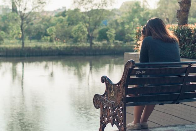 Грустная, расстроенная и взволнованная женщина, сидящая одна на улице Premium Фотографии