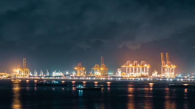 夜に貨物船積み港で出荷コンテナーをロードするクレーンのパノラマビュー Premium写真