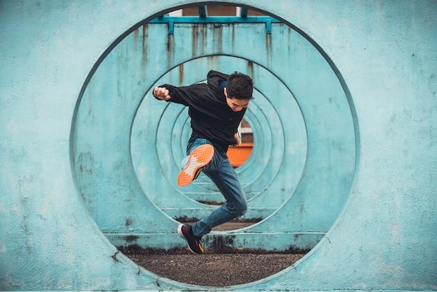 ジャンプしてアクションを蹴る若いアジアアクティブな男 Premium写真