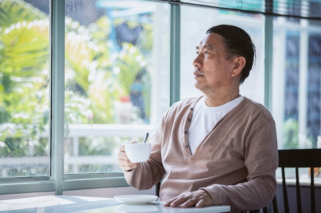 アジアのシニア男性の肖像画は、コーヒーのマグカップを探していると思考の概念を保持します。 Premium写真