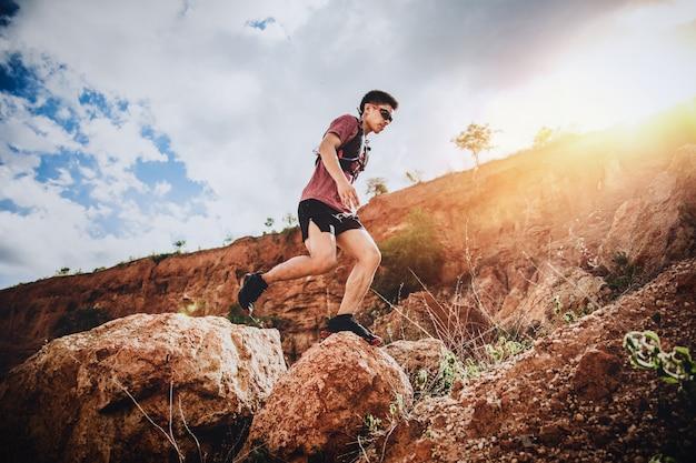 地平線と石の上をジャンプトレイルランナー Premium写真