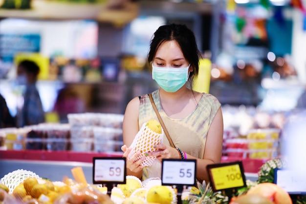 医療フェイスマスクのアジアの女性は、スーパーで買い物しながら果物を選択します。コロナウイルスの概念 Premium写真