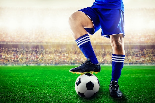 スタジアムでのキックオフのためのサッカーボールの青チームサッカー選手のフィート Premium写真