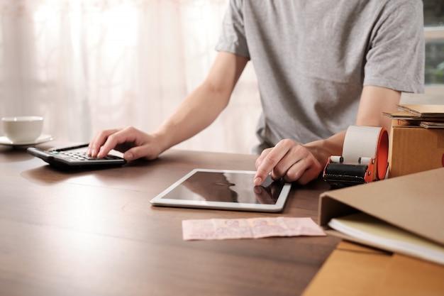 若いスタートアップのビジネスオーナーは午前中にタブレットで注文を確認しています Premium写真