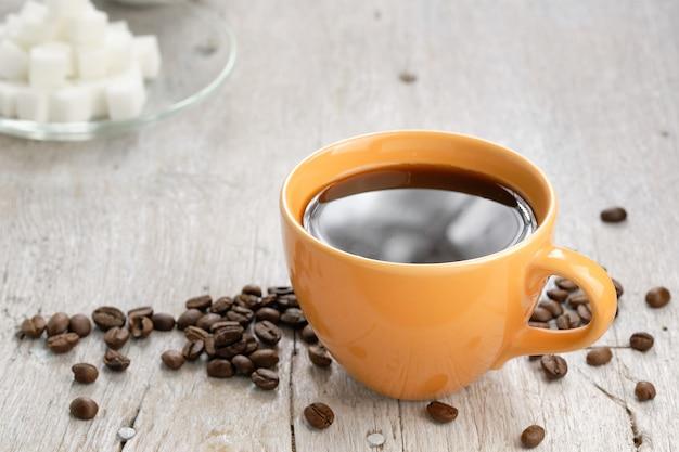 Апельсиновая кофейная чашка, кусочек сахара и кофейные зерна, некоторые части были налиты на деревянный стол. Premium Фотографии