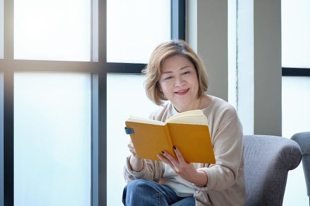 コーヒーを飲みながらリラックスした日に窓辺で本を読んでいる高齢者の女性。 Premium写真