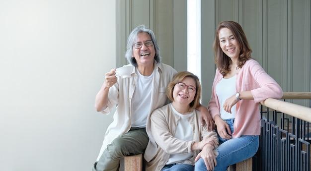 両親と娘は、家族の中で一緒に写真を撮りながら、リビングルームでお互いを喜んで受け入れます。 Premium写真