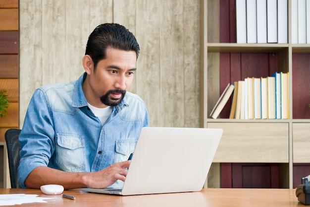 ハンサムなひげを生やした男は座って、机でノートパソコンを使用しています。 Premium写真