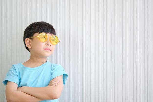 Азиатский милый мальчик мечтает носить желтые очки Premium Фотографии